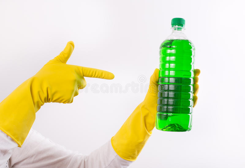Index finger pointing on cleaning product. Human hand with rubber gloves pointing index finger on green liquid detergent in transparent bottle. Isolated on white royalty free stock photo
