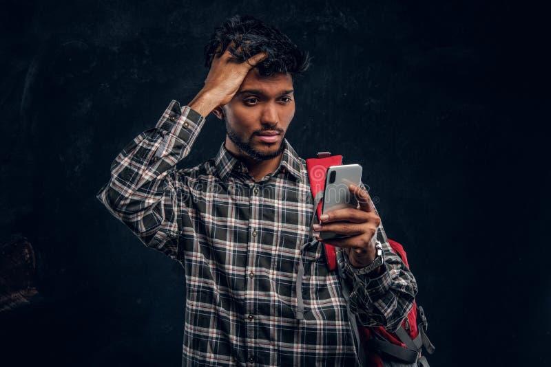 Indiański uczeń z plecakiem zapominał o coś bardzo znacząco i z spojrzenia sfrustowanymi spojrzeniami przy jego smartphone obrazy royalty free