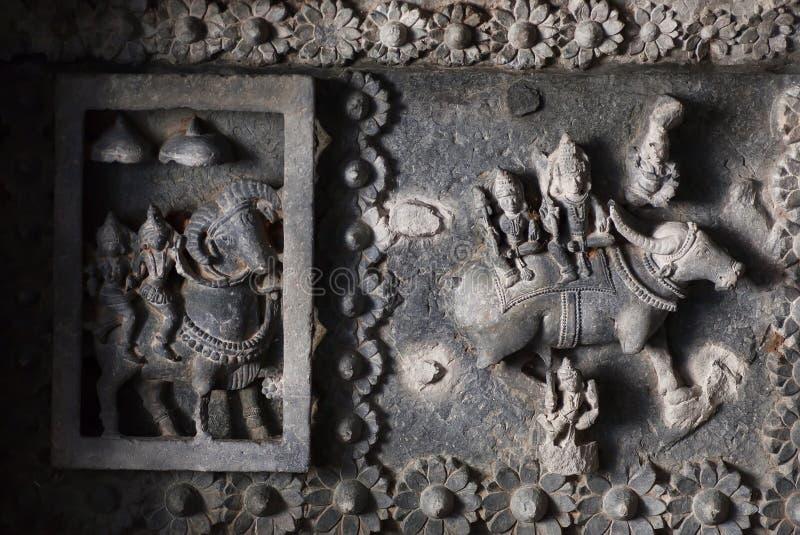 Indiańscy bóg Siva i Parvati na suficie 12th wiek świątynny Hoysaleswara z fantastycznymi cyzelowaniami zdjęcie stock