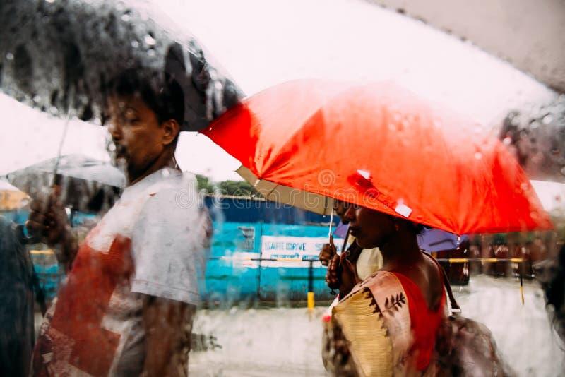 Indiańscy ludzie chodzi w deszczu z parasolem, widoku i strumieniu, przez samochodu okno z deszcz kroplami obraz royalty free