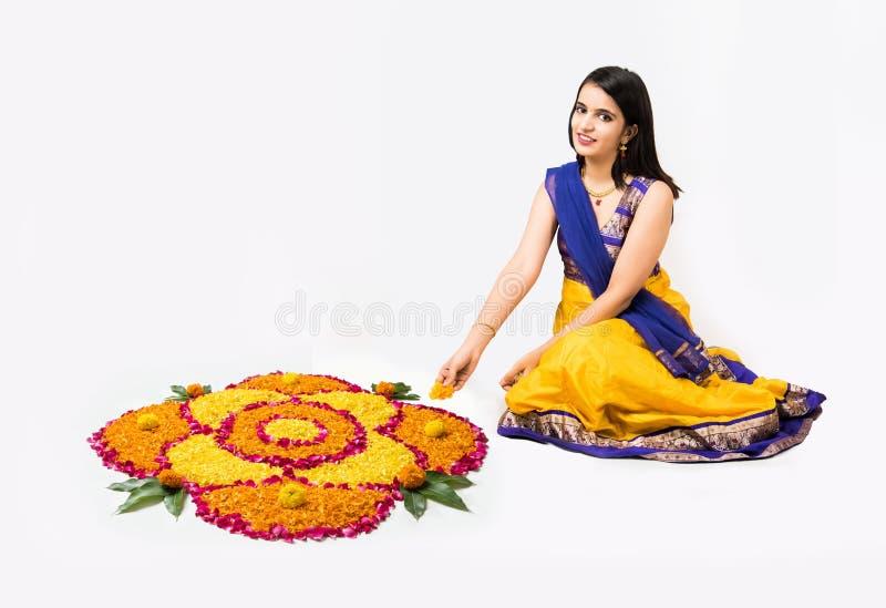 Indiańska kobieta, młoda dziewczyna robi kwiecistymi lub kwiatu rangoli dla diwali lub onam, odizolowywający nad białym tłem zdjęcie royalty free