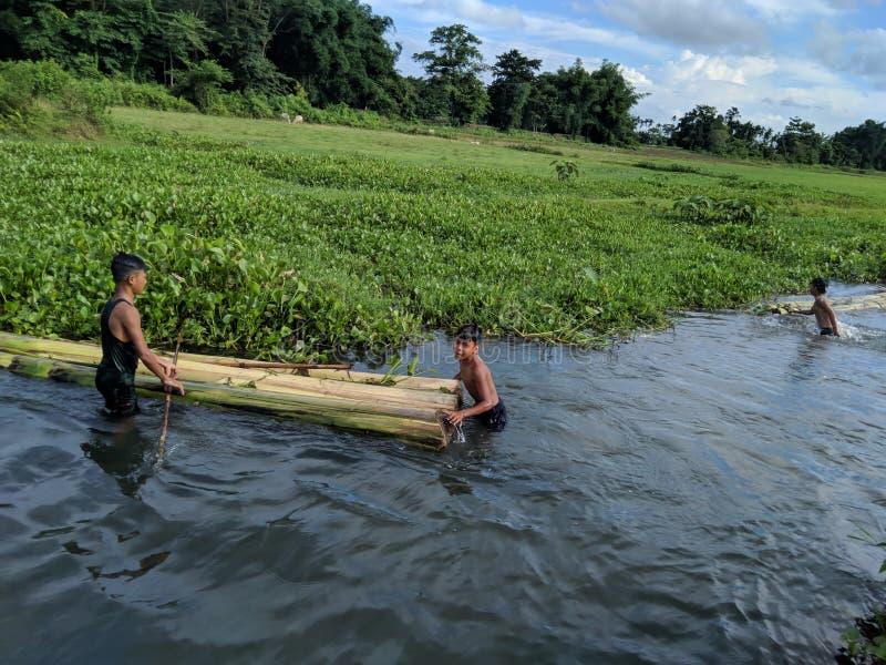 Indiańska wioska żartuje cieszyć się z ich handmade Bananową łodzią na lato czasie przy Tinsukia, Assam, India na 21st 2019 Czerw fotografia stock