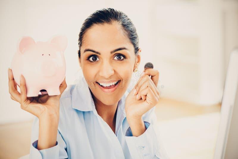 Indiański biznesowej kobiety oszczędzania pieniądze prosiątka bank obrazy stock
