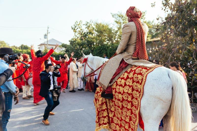 Indiański fornal pozbywa się białego konia z deseniową tkaniną, kwiat kolią i czerwień turbanem z gościami koloru żółtego i czerw fotografia stock
