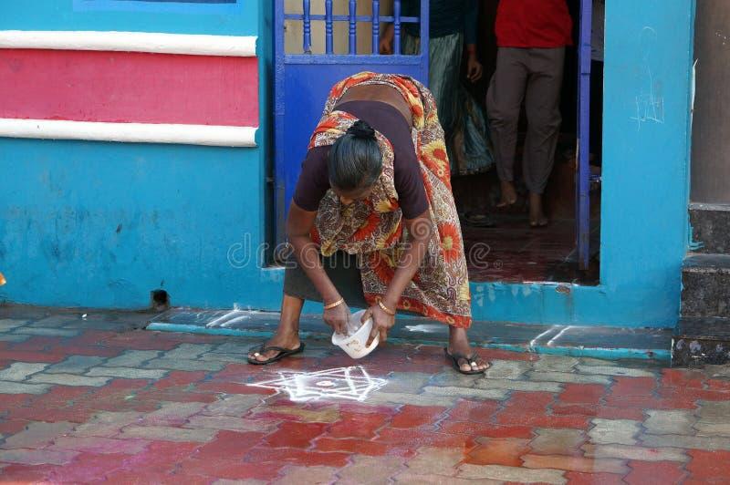 Indiański kobiet poz mąki znak Rangoli na jego progu, filmującym w mieście Rameswaram, India, w Grudniu 2013 fotografia stock