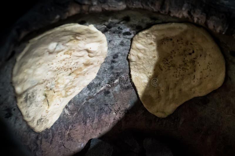 Indiański płaski chlebowy «Naan» robi w oryginalnym India tandoori gliny piekarniku zdjęcia royalty free