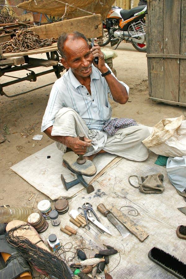 Indiański stary człowiek opowiada na jego telefonie komórkowym w jego cobbler sklepie obrazy stock