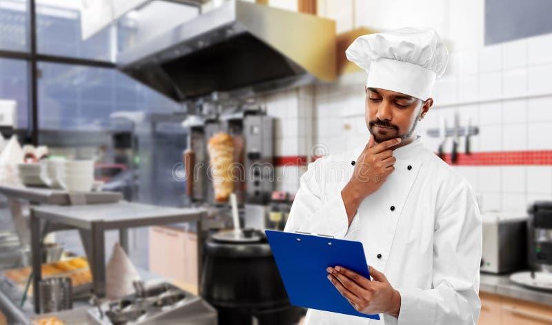 Indiański szef kuchni z menu na schowku przy kebabu sklepem obraz royalty free
