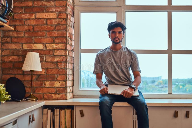 Indiański uczeń trzyma laptop podczas gdy siedzący na nadokiennym parapecie w studenckim dormitorium obraz royalty free