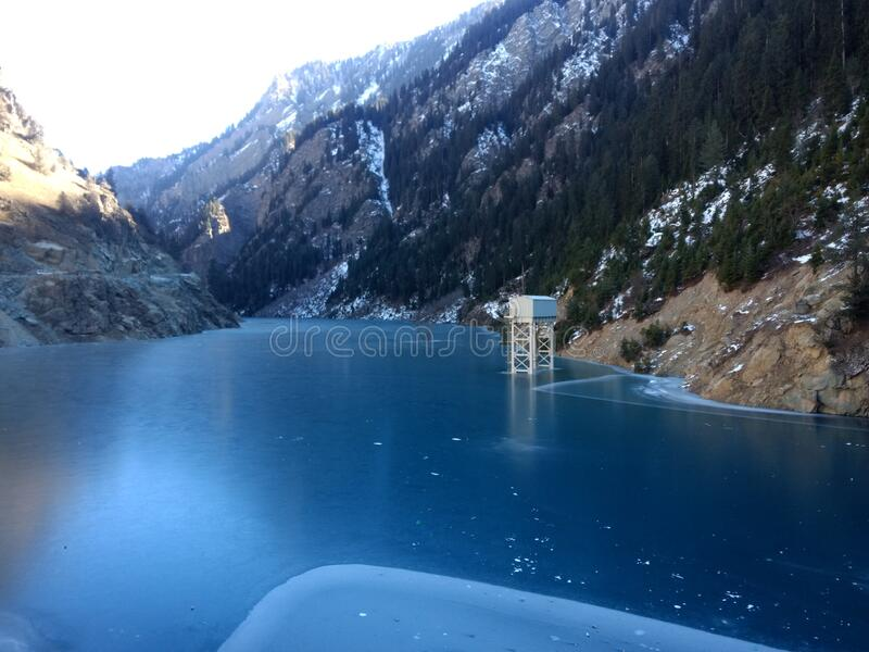India Deep blue frozen water lake in winter and steel Structure. India Jammu & Kashmir at kishanganga river Deep Blue Frozen water at reservoir of Dam and snow stock images