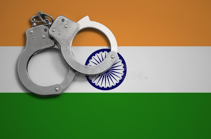 India flag and police handcuffs. The concept of crime and offenses in the country.  stock photography