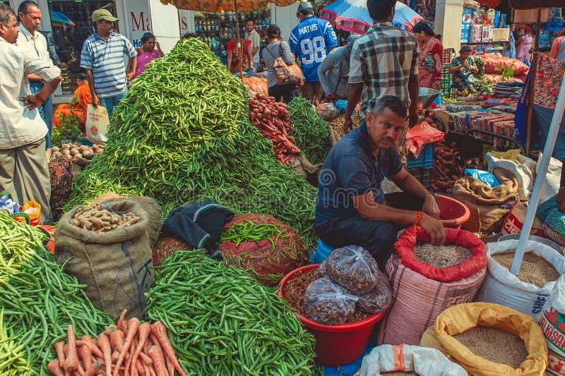 India, Goa - Februari 9, 2017: De mens verkoopt groenten op de markt stock foto's