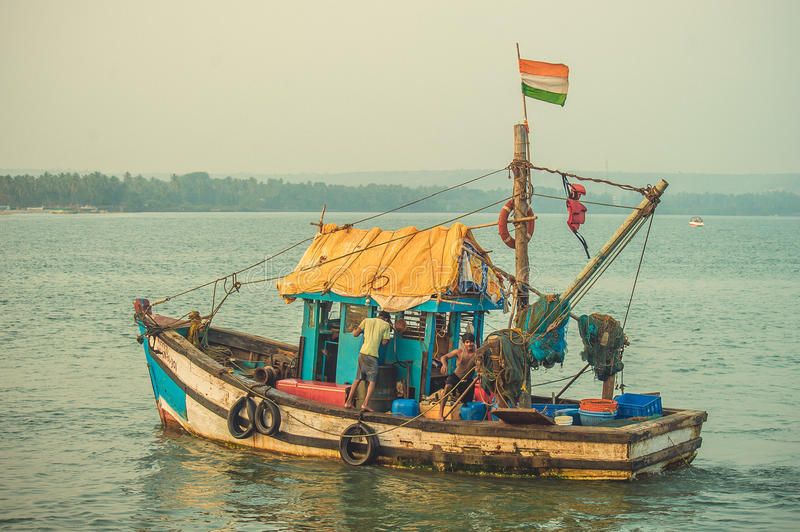 India, Goa - February 2, 2017: A fishing boat with an Indian flag sails into the sea.  stock photography