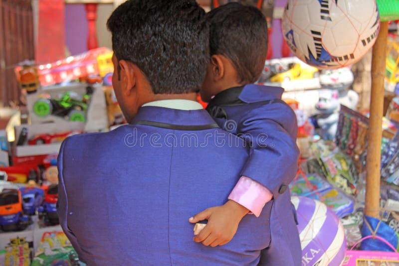 India, GOA, 28 Januari, 2018 Een zoon in de handen van zijn vader, houdt Indische Roepies in zijn hand stock afbeeldingen