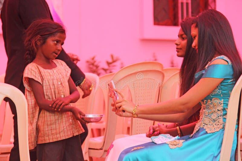 India, GOA, 28 Januari, 2018 Het slechte kind vraagt geld van voorbijgangers, kind met uitgestrekte hand, bedelaar Armoede in Ind stock foto's