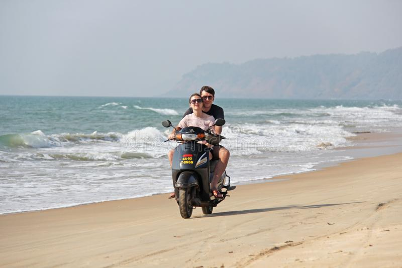 India, GOA, January 22, 2018. A girl and a guy are riding a scooter along the seashore. Scooter on the beach.  stock photos