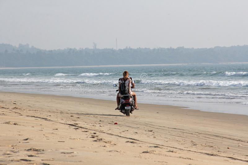 India, GOA, January 22, 2018. A girl and a guy are riding a scooter along the seashore. Scooter on the beach.  royalty free stock image