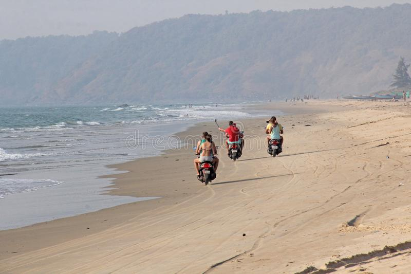 India, GOA, January 22, 2018. A girl and a guy are riding a scooter along the seashore. Scooter on the beach.  stock photography