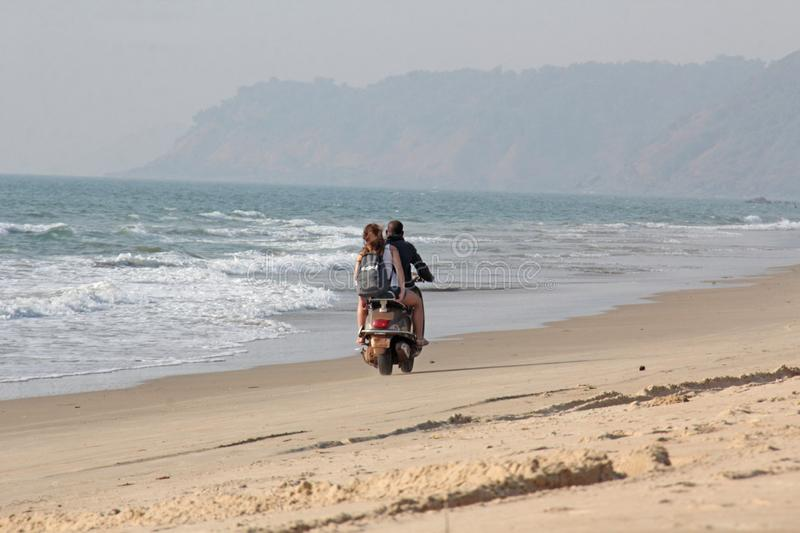 India, GOA, January 22, 2018. A girl and a guy are riding a scooter along the seashore. Scooter on the beach.  royalty free stock photos