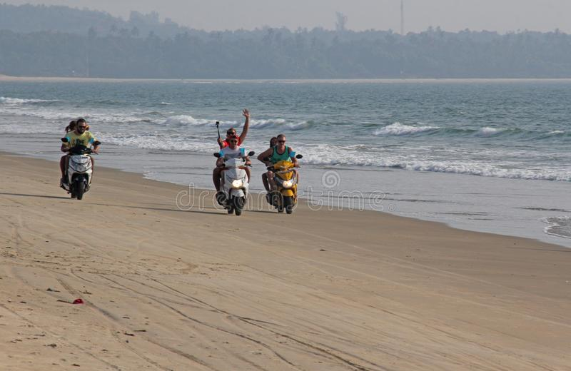 India, GOA, January 22, 2018. A girl and a guy are riding a scooter along the seashore. Scooter on the beach.  stock images