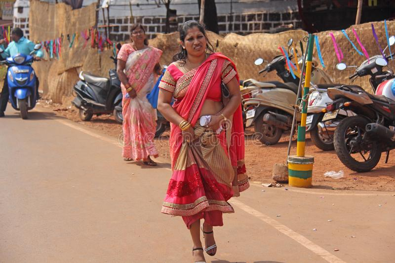 India, GOA, January 28, 2018. An Indian woman in a bright red and beautiful sari is walking along the street.  stock images