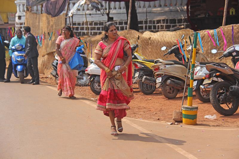 India, GOA, January 28, 2018. An Indian woman in a bright red and beautiful sari is walking along the street.  royalty free stock images