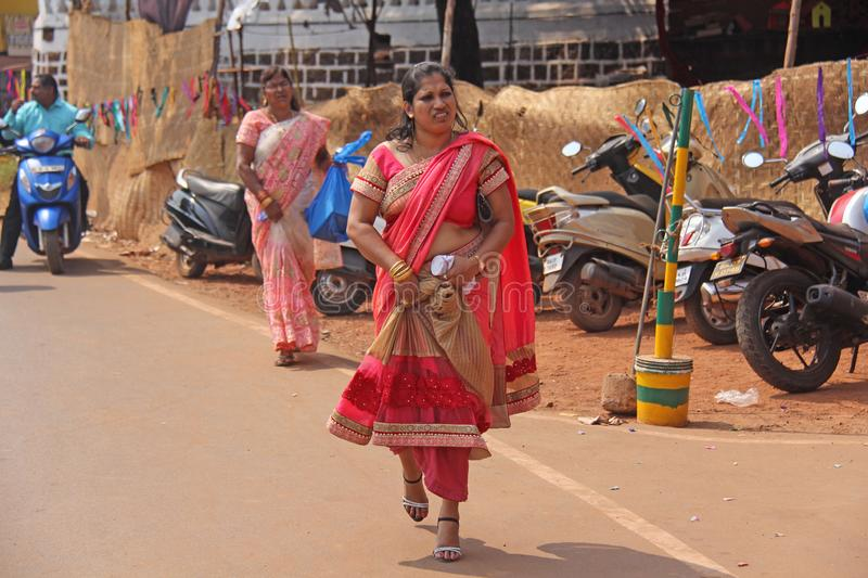 India, GOA, January 28, 2018. An Indian woman in a bright red and beautiful sari is walking along the street.  royalty free stock photos