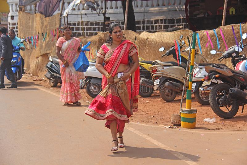 India, GOA, January 28, 2018. An Indian woman in a bright red and beautiful sari is walking along the street.  royalty free stock photo