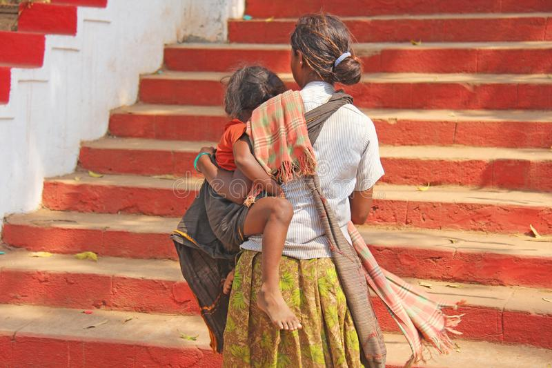 India, GOA, January 28, 2018. Indian woman with a child in her arms with her back. Poor people in India. Poverty.  stock photography