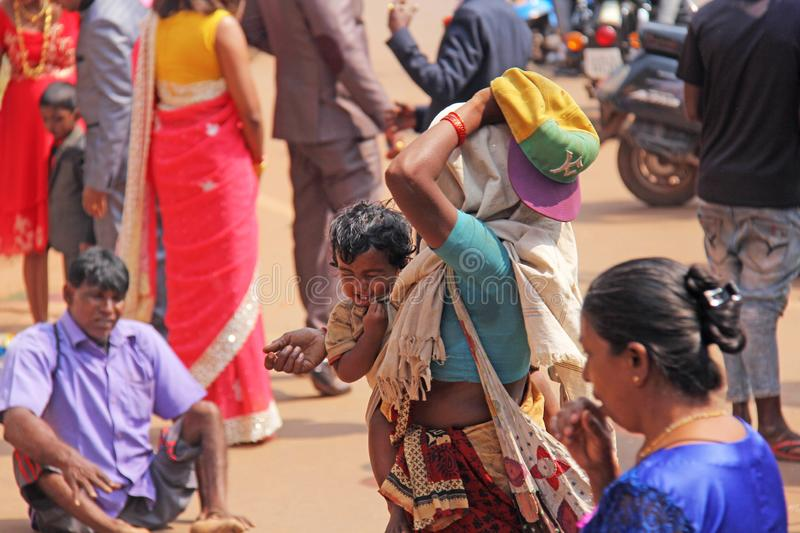 India, GOA, January 28, 2018. Poor woman with a child asks for money on the street in India. A beggar woman with an outstretched. Hand. Poverty royalty free stock photography