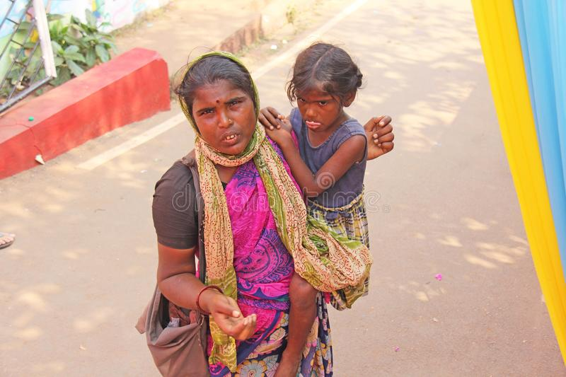 India, GOA, January 28, 2018. Poor woman with a child asks for money on the street in India. A beggar woman with an outstretched. Hand. Poverty stock photo