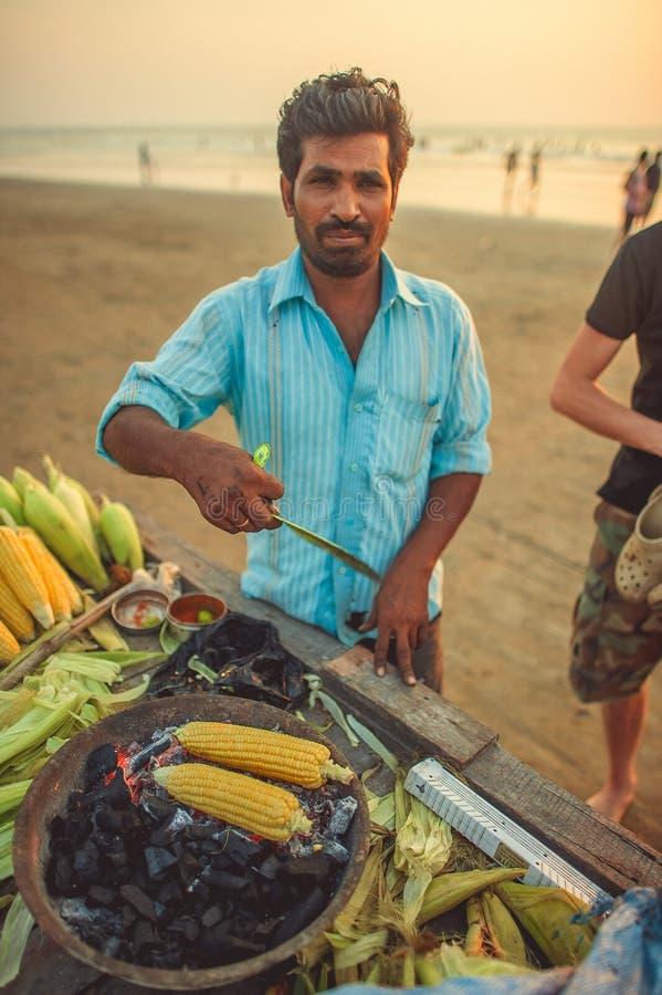 India Goa, Listopad, - 26, 2016: Mężczyzna jest kulinarnym kukurudzą na węglu drzewnym zdjęcia stock