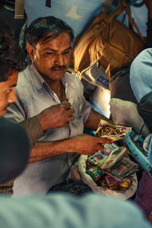INDIA, GRUDNIA 2012 Niezidentyfikowany mężczyzna robi foods dla pasażerów wśrodku Indiańskiego Kolejowego lokalnego pociągu na Gr zdjęcie royalty free
