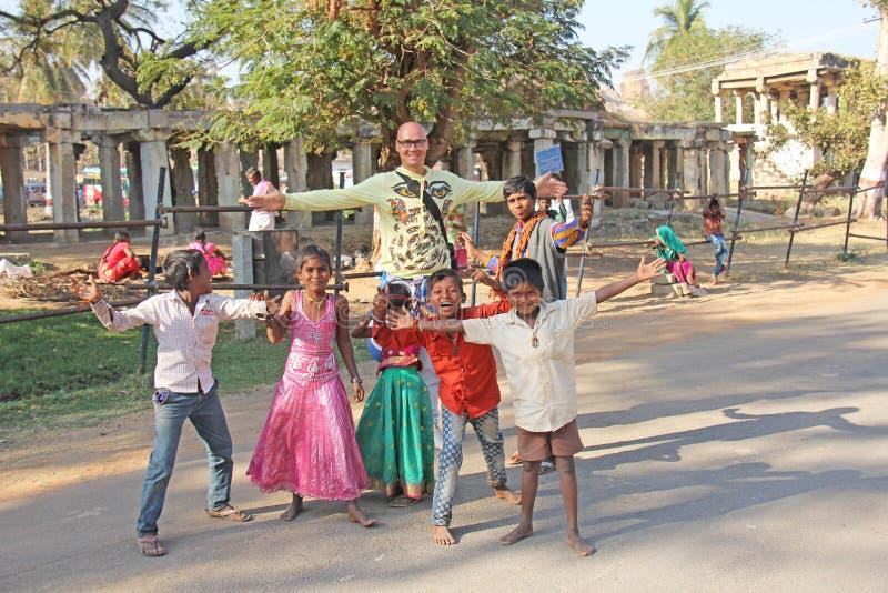 India, Hampi, 02 February 2018. A bald and cheerful European man dances with children from India. Joyful children of India. Hampi. Vijayanagar, karnataka stock image