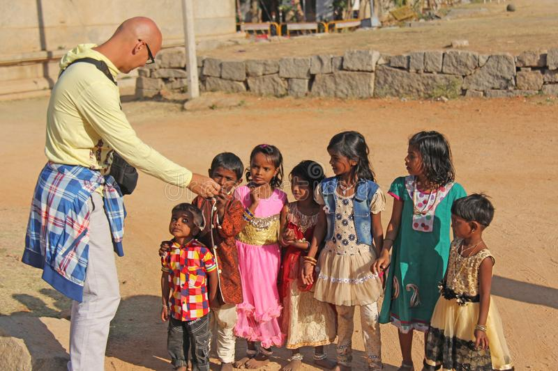 India, Hampi, 02 February 2018. A bald and cheerful European man gives gifts to Indian children. Joyful children are pulling their stock photo