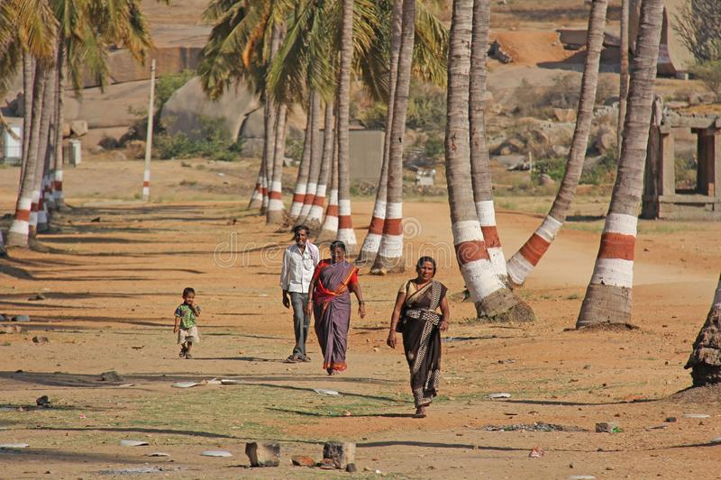 India, Hampi, 02 February 2018. Children, men and women in a sari walk in a palm grove. People of India.  royalty free stock image