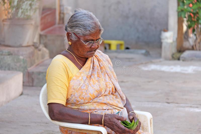 India, Hampi, February 2, 2018. An elderly Indian woman in a sari sits on a chair.  stock photo