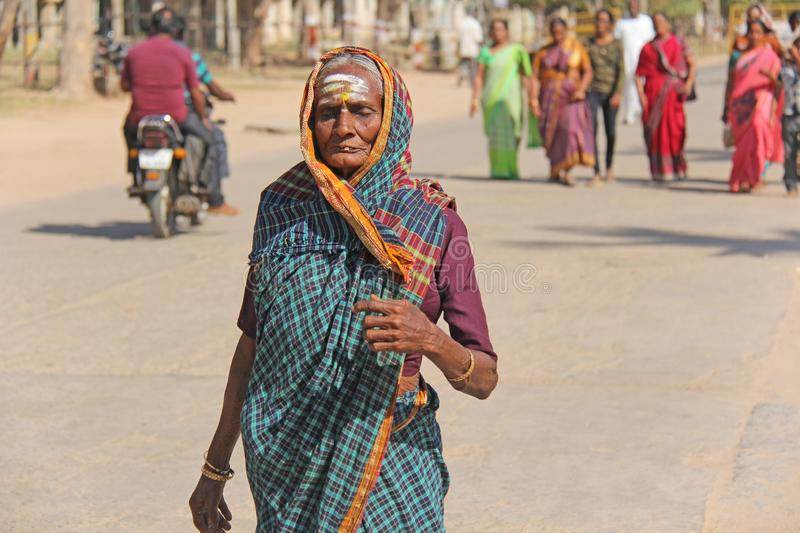 India, Hampi, February 2, 2018. An elderly woman in a sari is walking along the street of Hampi village. The Indian woman is. Rubbed. Hampi, Vijayanagar royalty free stock photography