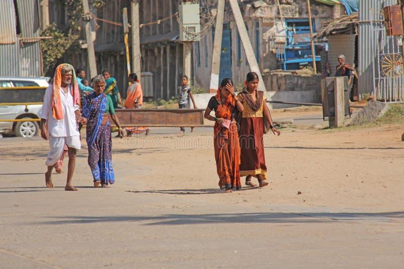India, Hampi, February 2, 2018. A group of people, men and women in the saris, walk along the street of Hampi village. Hampi,. Vijayanagar, karnataka, unesco stock images