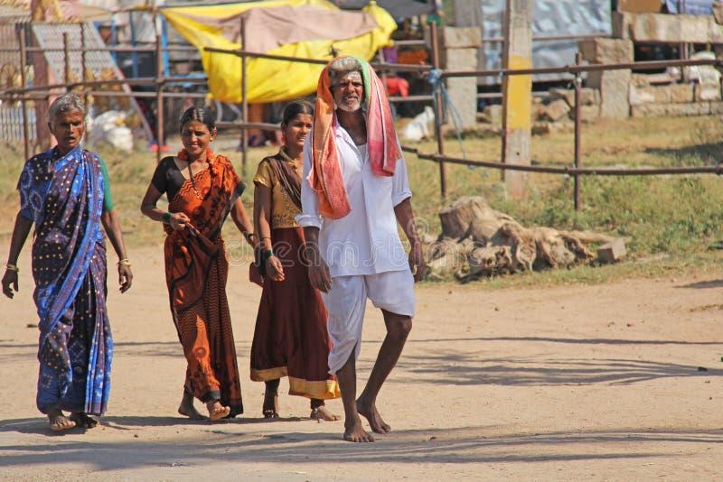 India, Hampi, February 2, 2018. A group of people, men and women in the saris, walk along the street of Hampi village. Hampi,. Vijayanagar, karnataka, unesco royalty free stock photography