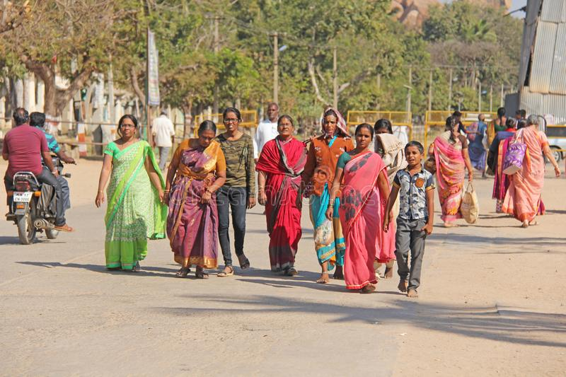 India, Hampi, February 2, 2018. A group of people, men and women in the saris, walk along the street of Hampi village. Hampi,. Vijayanagar, karnataka, unesco stock photo