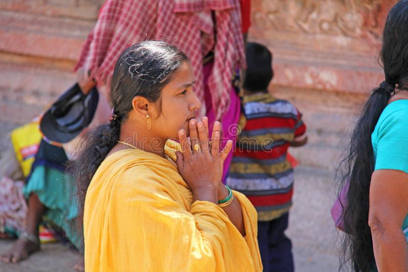 India, Hampi, 01 February 2018. An Indian woman in a bright yellow sari folded her arms in a namaste.  stock image