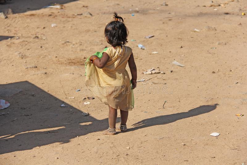 India, Hampi, 02 February 2018. A little poor girl in a dirty dress.  stock photo