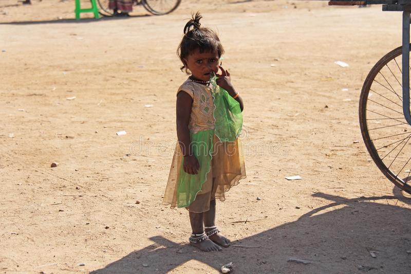 India, Hampi, 02 February 2018. A little poor girl in a dirty dress. Portrait of an indian girl. A girl from India in ornaments.  royalty free stock photography