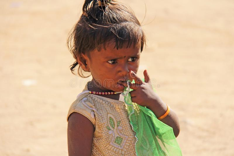 India, Hampi, 02 February 2018. A little poor girl in a dirty dress. Portrait of an indian girl. A girl from India in ornaments.  stock image