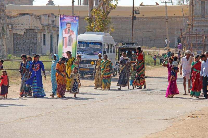 India, Hampi, 02 February 2018. The main street of Hampi village is women in sari, men, children, a group of people. Indian people. Motorcycle stock photo