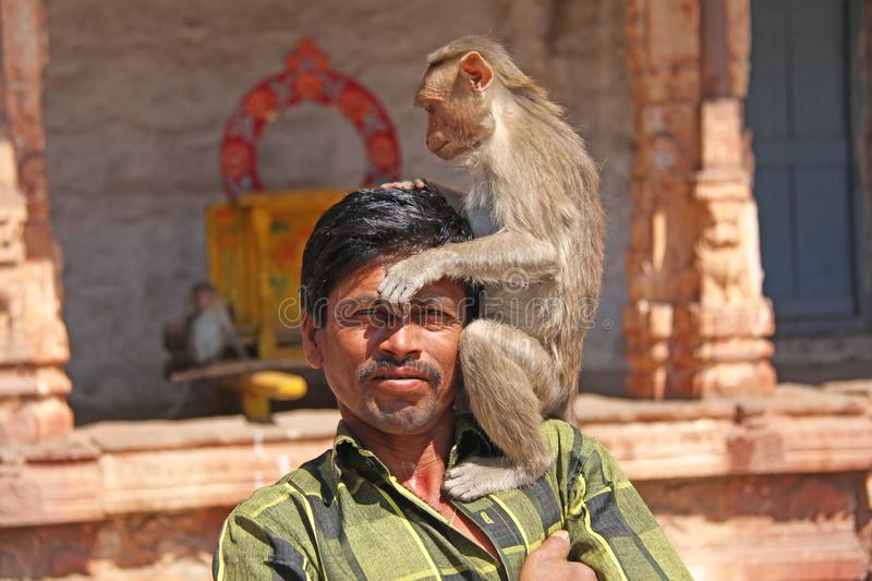 India, Hampi, 01 February 2018. The monkey sits on the shoulder of an Indian man. Close-up portrait royalty free stock photography