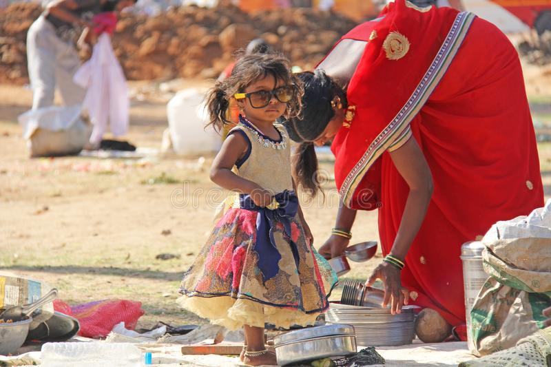 India, Hampi, 02 February 2018. A small poor and dirty Indian girl playing with sunglasses. A little girl in big glasses from the. Sun. The girl is a royalty free stock image