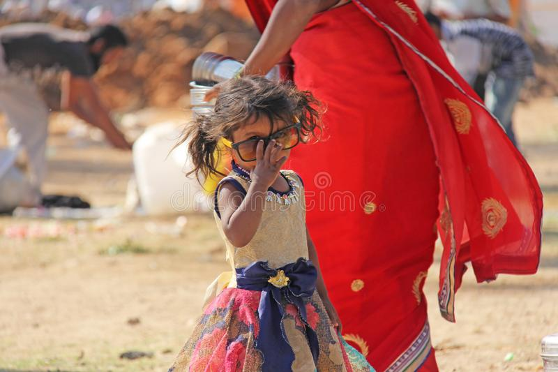 India, Hampi, 02 February 2018. A small poor and dirty Indian girl playing with sunglasses. A little girl in big glasses from the. Sun. The girl is a stock photography