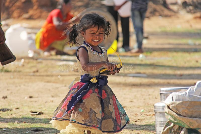 India, Hampi, 02 February 2018. A small poor and dirty Indian girl playing with sunglasses. A little girl in big glasses from the. Sun. The girl is a royalty free stock photo
